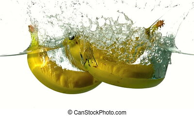 Bunch of bananas plunging into water on white background in...