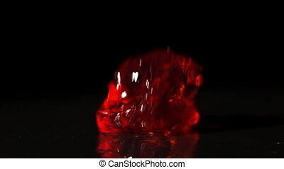 Red jelly falling and bouncing on black background in slow...