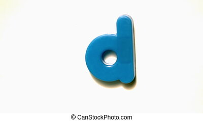 Blue letter d lifting off white background in slow motion