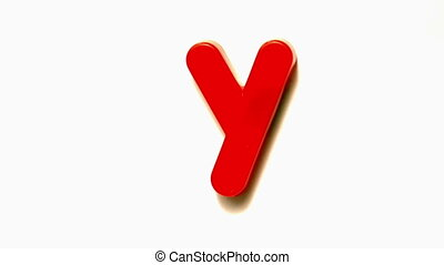 Red letter y lifting off white background in slow motion