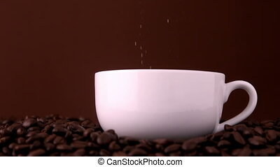 Sugar pouring into white coffee cup in slow motion
