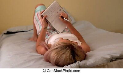 Pretty young blonde writing in notepad on her bed in slow...