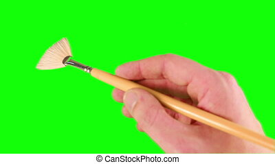 Artist painting with paint brush on green screen background
