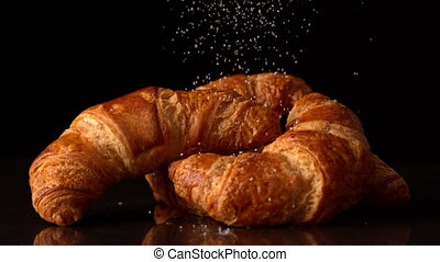 Powdered sugar sprinkling onto croissants in slow motion