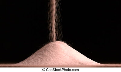Sugar pouring on black background in slow motion
