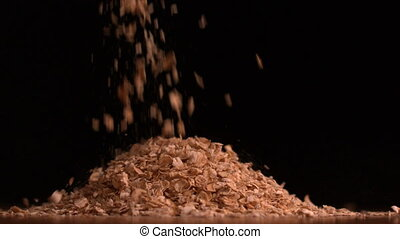 Cereal flakes pouring on black bac