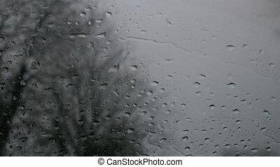 Rain falling onto car windshield in slow motion