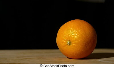 Knife slicing orange in half - Knife slicing orange in half...