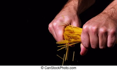 Hands snapping spaghetti in half in slow motion