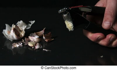 Hand using garlic press on black background in slow motion