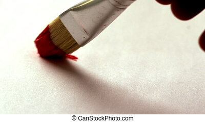 Painter painting with red paint and paintbrush in slow...