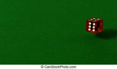 Red dice rolling on casino table in slow motion