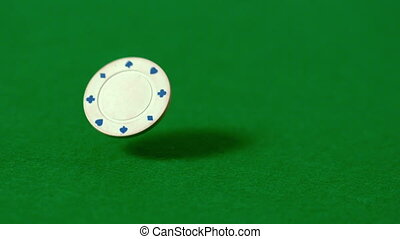 Casino chips falling on green table