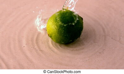Lime spinning on wet white surface in slow motion