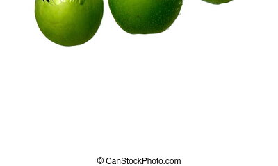 Green apples plunging into water on white background in slow...