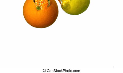 Orange and lemon plunging into water on white background in...
