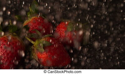 Water pouring over punnet of strawberries in slow motion