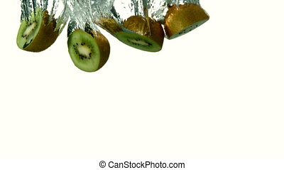 Kiwi pieces plunging into water on white background in slow...