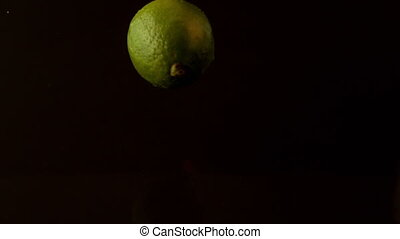 Lime dropping on wet black surface in slow motion