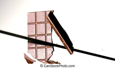 Arrow shooting through a chocolate bar in slow motion