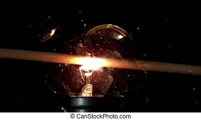 Arrow shooting through light bulb in slow motion