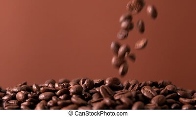 Coffee beans pouring onto pile in slow motion