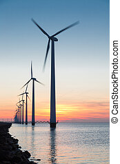 Dutch row offshore wind turbines at beautiful sunset - Long...