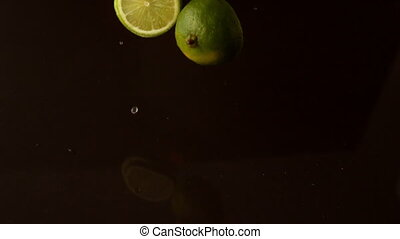 Lime pieces dropping on wet black surface in slow motion