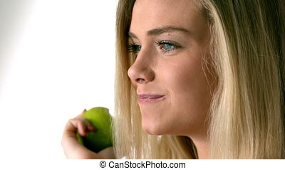 Pretty blonde eating a green apple