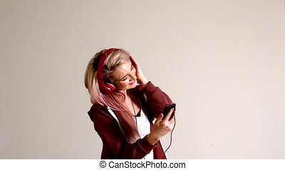 Sporty blonde listening to music with smartphone in slow...