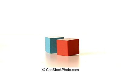 Building blocks sliding across surface and hitting in slow...