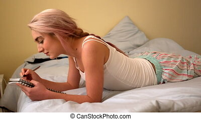 Pretty young blonde lying on bed writing in notepad in slow...