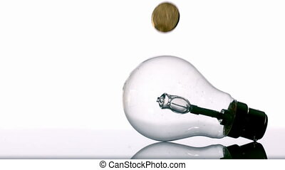 Euro coins falling into light bulb in slow motion