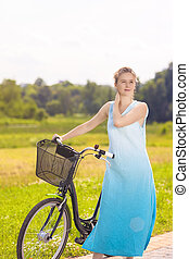 Portrait of Young Happy Caucasian Blond With Female Bicycle in the Park on a Sunny Day. Vertical Image