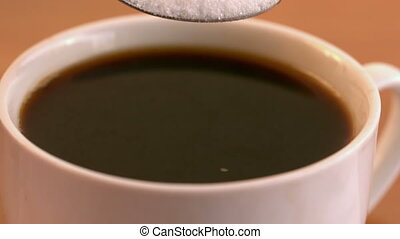 Teaspoon of sugar plunging into coffee