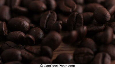 Coffee beans pouring onto wooden surface in slow motion