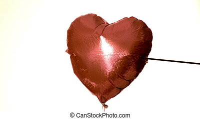 Arrow shooting through heart balloon on white background in...