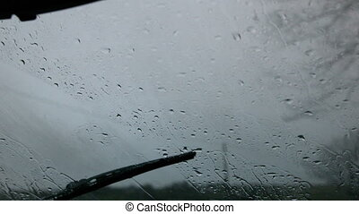 Windscreen wiper wiping rain away from car window in slow...