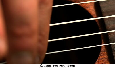 Hand strumming guitar strings close up in slow motion