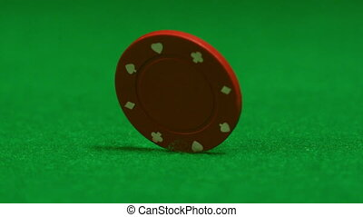 Red chip spinning on casino table in slow motion
