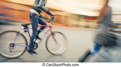 Cyclists and pedestrians in the city. Young people going...