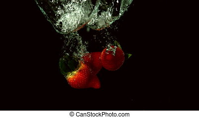Strawberries falling in water on black background in slow...