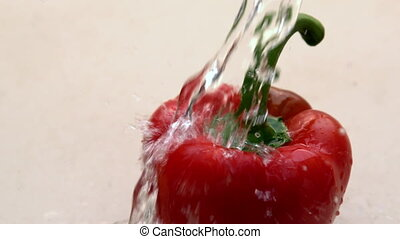 Water pouring on red pepper in slow motion