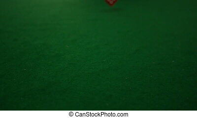 Red dice rolling towards camera on casino table in slow...