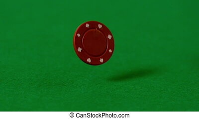 Casino chips falling on green table in slow motion