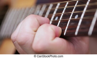 Men's Fingers on odds - Female hand holding guitar frets