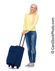 smiling young woman with suitcase - travel and vacation...
