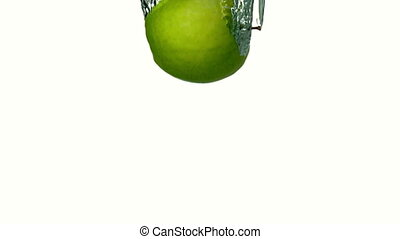 Green apple plunging into water on white background in slow...