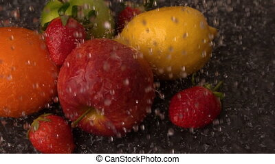 Water raining on selection of fresh fruit in slow motion