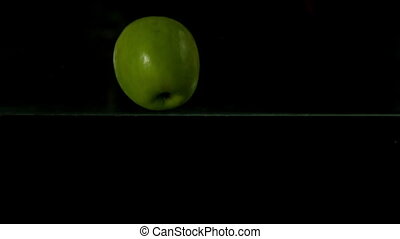 Green apple plunging into water on black background in slow...